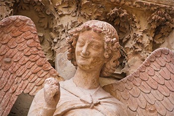 Reminder: Angels In The Bible Were Mind-Melting Horror Beasts - the smiling cherub from the Reims Cathedral in France