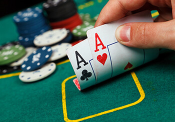 Essential Tips For Your First Stand Up Comedy Open Mic  a person playing poker with pocket aces