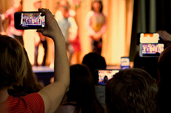 Essential Tips For Your First Stand Up Comedy Open Mic  people filming a comedy show on their phones