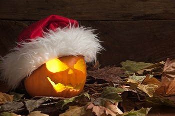 5 Unspoken Reasons The Holidays Suck For Millions Of Americans - a jack-o-lantern wearing a Santa hat