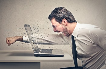 5 Unspoken Reasons The Holidays Suck For Millions Of Americans - a man punching his fist through a laptop