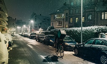 5 Unspoken Reasons The Holidays Suck For Millions Of Americans - a deliveryman riding a bicycle on a night with sleet