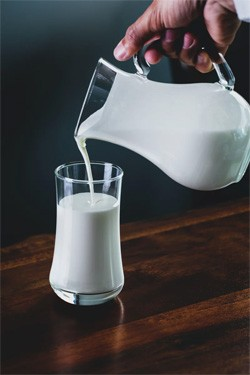 5 'Good' Ideas That Are Secretly Propaganda - a hand pouring a pitcher of milk into a glass