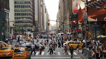 New York City streets with people walking through traffic.