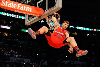Photograph of Blake Griffin dunking and hanging from the rim wearing a red Los Angeles jersey with the number 32