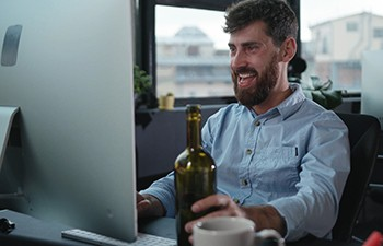 6 Ways Breaking into Hollywood Is A Total Nightmare - man drinking a bottle of whiskey while typing at computer