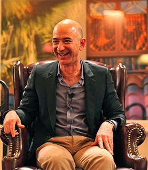 5 Rich People Who Prove Wealth Makes You Weird - Jeff Bezos smiling and sitting in a chair