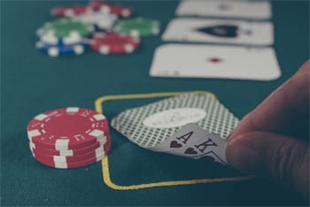 5 Hollywood-Worthy Twists That Saved People's Lives - man flipping over cards during a game of poker